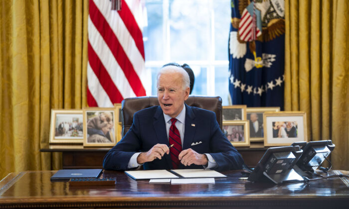 President Joe Biden signs executive orders in the Oval Office of the White House in Washington, on Jan. 28, 2021. (Doug Mills-Pool/Getty Images)