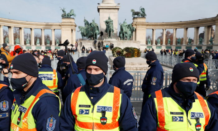Police officers stand during a demonstration against the coronavirus disease (COVID-19) measures and their economic consequences at Heroes' Square in Budapest, Hungary, on Jan. 31, 2021. (Bernadett Szabo/Reuters)
