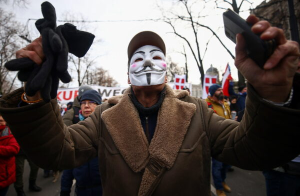 A man wearing a mask gestures during a demonstration