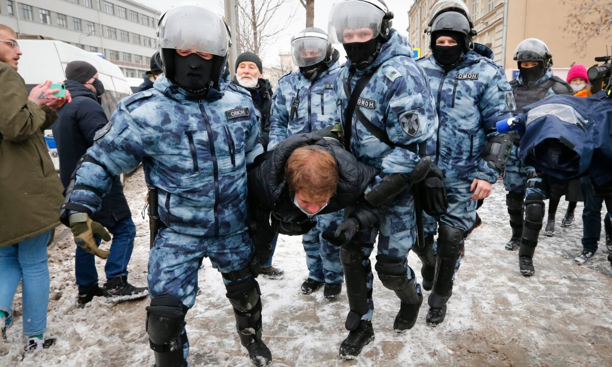 Police officers detain a man during a protest against the jailing of opposition leader Alexei Navalny in Moscow