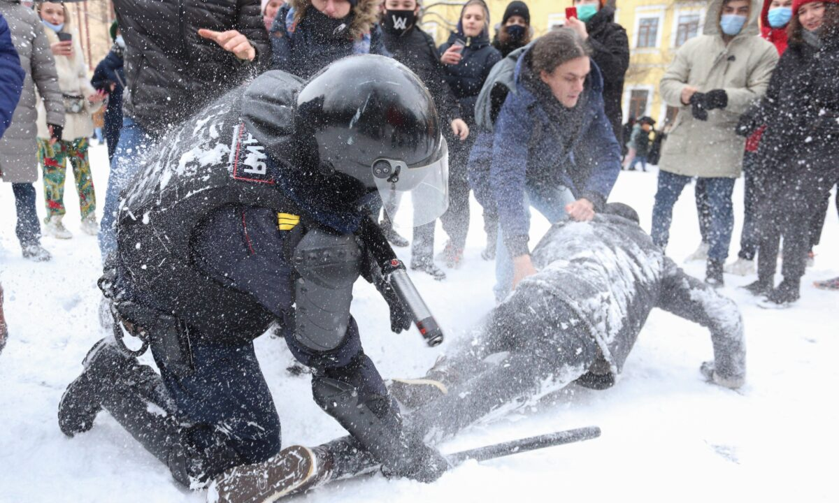 A policeman detains a man while protesters try to help him
