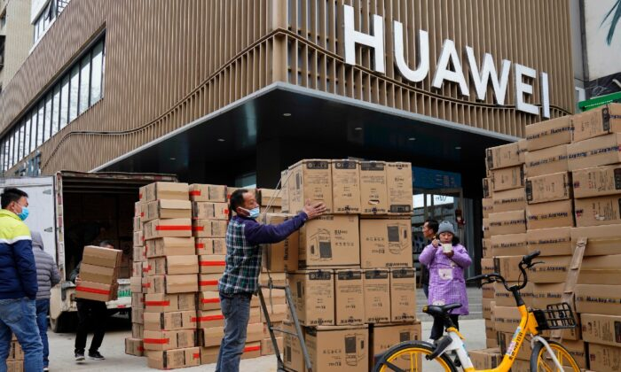 Workers move boxes of computers on a street of Wuhan in central China's Hubei province on Jan. 16, 2021. (Ng Han Guan/AP)