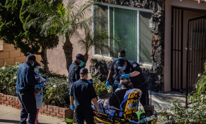 County of Los Angeles paramedics administer oxygen to a potential COVID-19 patient on the sidewalk in front his building before taking him to a hospital in Hawthorne, Calif., on Jan. 21, 2021. (Apu Gomes/Getty Images)