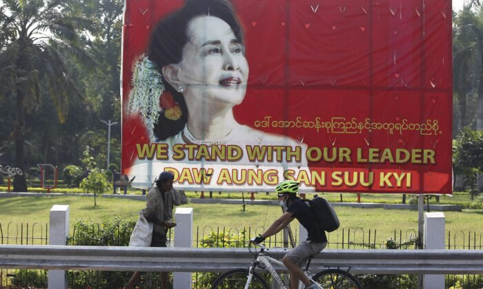 A cyclist bikes past a signboard with an image of Myanmar leader Aung San Suu Kyi, in Yangon, Myanmar, on Jan. 29, 2021. (Thein Zaw/AP Photo)