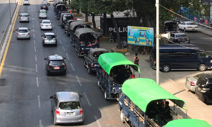 Myanmar police vehicles drive near the City Hall in Yangon, Myanmar, on Feb. 1, 2021. (Stringer/Reuters)