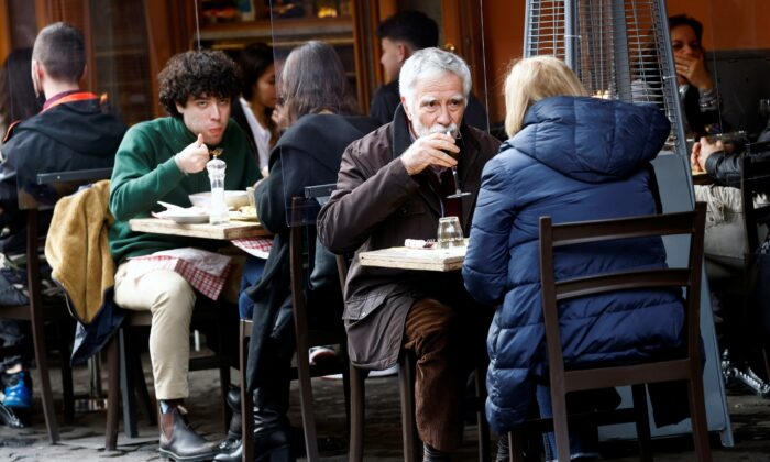 People sit at a restaurant in Trastevere after the COVID-19 restrictions were eased in the Lazio region, Rome, Italy, on Feb. 1, 2021. (Guglielmo Mangiapane/Reuters)