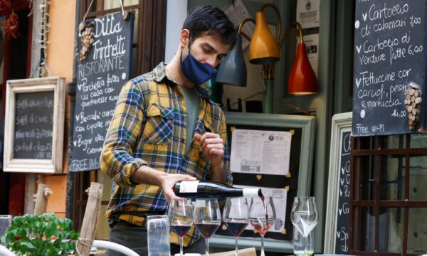 Staff member pours wine at a restaurant
