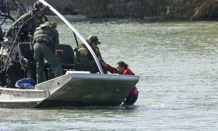 Agents on a U.S. Customs and Border Protection boat rescue a woman and child who got stuck attempting to cross the Rio Grande into the United States illegally at Eagle Pass, Texas, on Feb. 16, 2019. (Charlotte Cuthbertson/The Epoch Times)