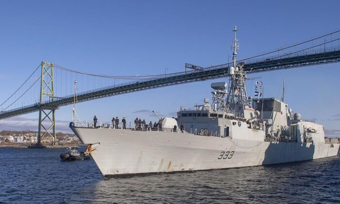 The Halifax-class frigate HMCS Toronto passes under the Angus L. Macdonald Bridge as it returns to Halifax on Dec. 23, 2020 after completing a six-month deployment in the Mediterranean Sea. (Andrew Vaughan/The Canadian Press)