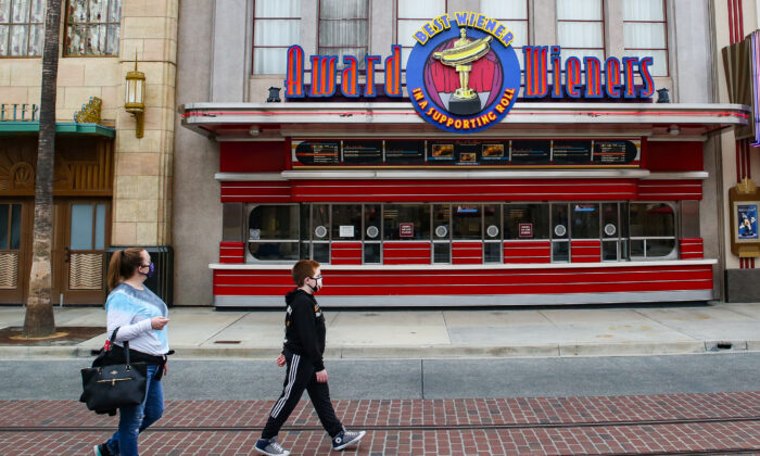 People walk by a closed hot dog shop at Disneyland California Adventure theme park in Anaheim, Calif., on Feb. 1, 2021. (John Fredricks/The Epoch Times)