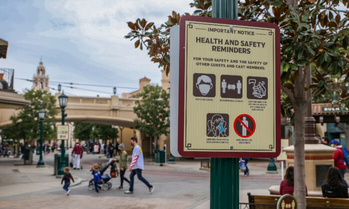 A family walks by a COVID-19 safety sign at Disneyland California Adventure themepark in Anaheim, Calif., on Feb. 1, 2021. (John Fredricks/The Epoch Times)