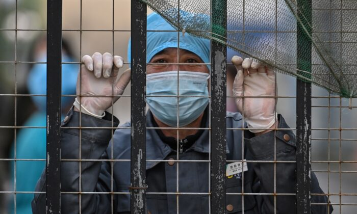 A worker wearing a face mask looks out from an entrance of a hospital toward the Wuhan centre for disease control and prevention in Wuhan, China's central Hubei province, China, on Feb. 1, 2021. (Hector Retamal/AFP via Getty Images)