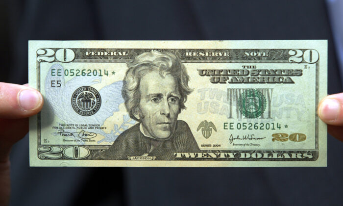 A $20 bill is held by a man in New York City on Oct. 9, 2003. (Chris Hondros/Getty Images)