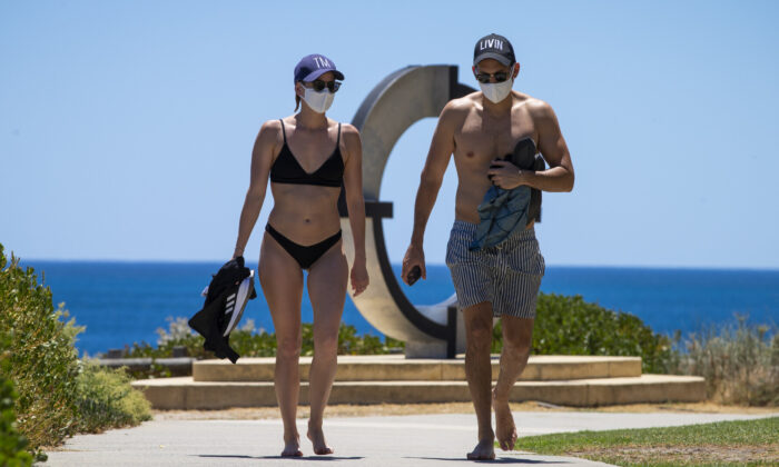 A young couple at Cottesloe Beach wearing mandatory face masks after an hour of recreational exercise is permitted in Perth, Australia on Feb. 1, 2021. (Matt Jelonek/Getty Images)