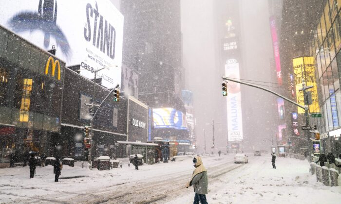 Pedestrians make their way through Times Square during a snowstorm, in the Manhattan borough of New York City on Feb. 1, 2021. (John Minchillo/AP Photo)
