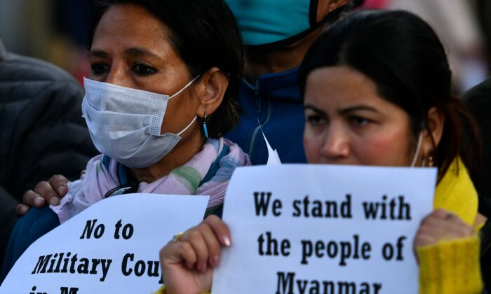 Protesters hold placards during a protest in Kathmandu, Nepal, on Feb. 1, 2021. (Prakash Matheema/AFP via Getty Images)
