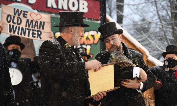 Groundhog Club handler A.J. Dereume holds Punxsutawney Phil, the weather prognosticating groundhog, as Vice President Tom Dunkel reads the scroll during the 135th celebration of Groundhog Day on Gobbler's Knob in Punxsutawney, Pa., on Feb. 2, 2021. (Barry Reeger/AP Photo)