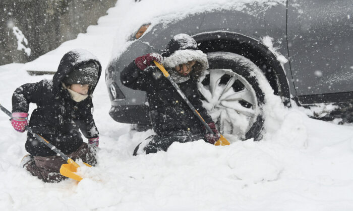 Perrin Sue Peters (L) and her sister Harlow Peters, of Pottsville, Pa., help their mother Aubrey shovel out her car in Pottsville, Pa., on Feb. 1, 2021. (Jacqueline Dormer/Republican-Herald via AP)