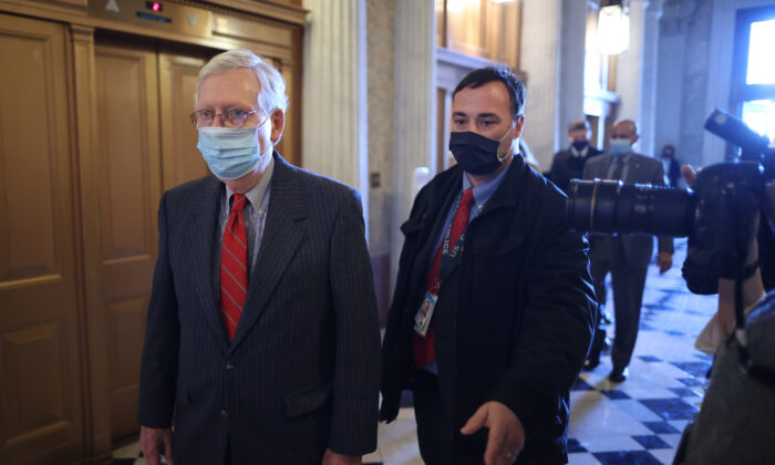 Senate Minority Leader Mitch McConnell (R-Ky.) (L) heads to the Senate Chamber at the U.S. Capitol in Washington on Jan. 28, 2021. (Chip Somodevilla/Getty Images)