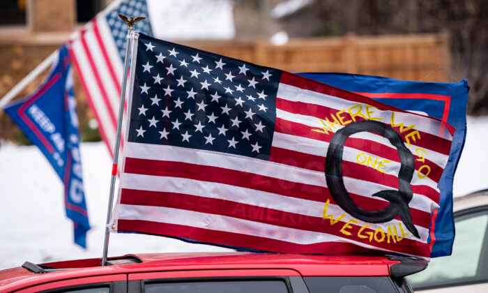 A car with a flag endorsing the QAnon drives by as supporters of President Donald Trump gather for a rally outside the Governor's Mansion on November 14, 2020 in St Paul, Minnesota. (Stephen Maturen/Getty Images)