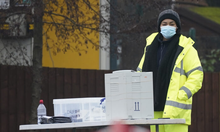 People hand in tests at a drive-in testing station as local authorities prepare to deploy COVID-19 testing in an effort to track down a South African CCP virus variant found in the area in Walsall, United Kingdom, Feb. 2, 2021. (Christopher Furlong/Getty Images)