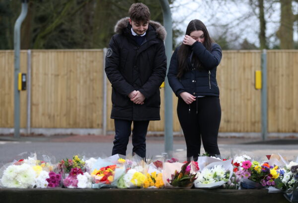 People look at flowers left near to the residence of Captain Sir Tom Moore