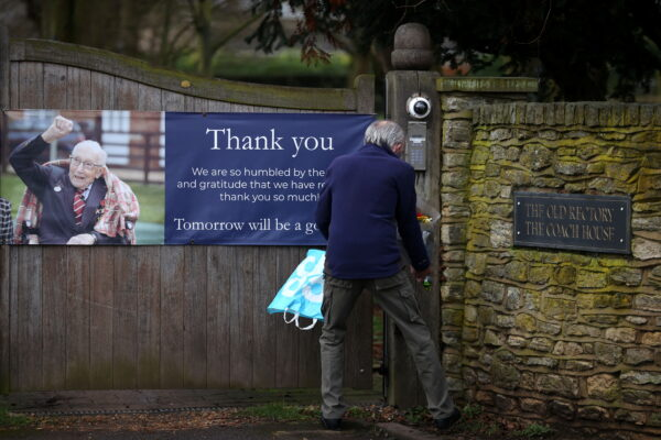 A person lays flowers at the gate to the residence of Captain Sir Tom Moore