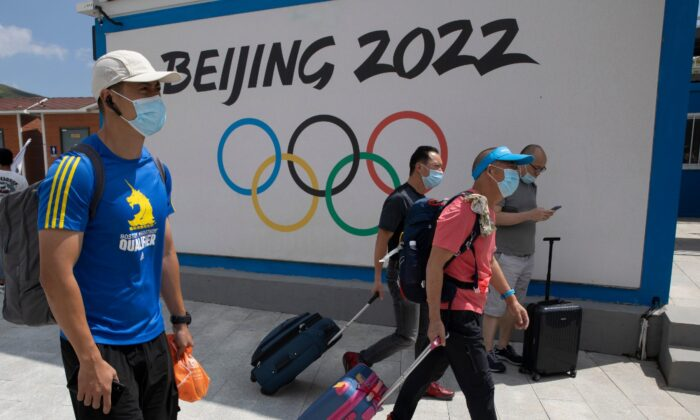 Visitors to Chongli, one of the venues for the Beijing 2022 Winter Olympics, pass by the Olympics logo in Chongli in Hebei Province, China, on Aug. 13, 2020. (Ng Han Guan/AP Photo)
