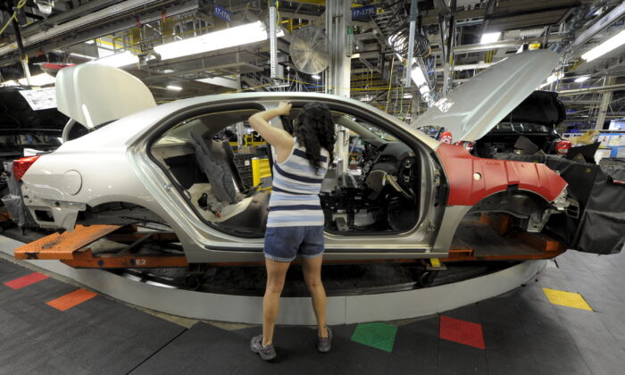 GM Auto worker Linda Martinez installs a part on a 2015 Chevrolet Malibu being built at GM's Fairfax assembly plant in Kansas City, Kans., on May 4, 2015. (Dave Kaup/Reuters)