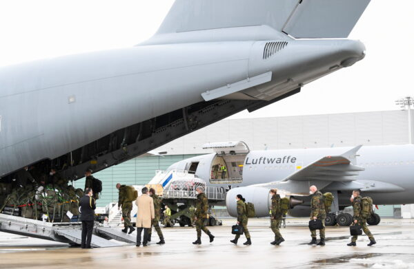 Staff members enter aboard an A400M military transport plane