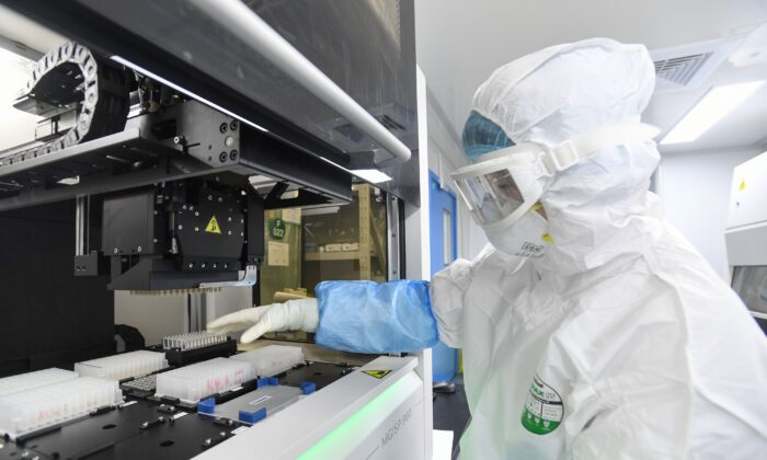 "This photo taken on Feb. 6, 2020, shows a laboratory technician working on samples from people to be tested for coronavirus at ""Fire Eye"" laboratory in Wuhan, China. BGI Group, a genome sequencing company based in southern China, said it opened on Feb. 5 a lab in Wuhan able to test up to 10,000 people per day for the virus. (STR/AFP via Getty Images)"