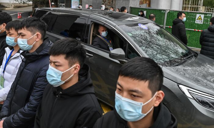 Members of the World Health Organization (WHO) team investigating the origins of the COVID-19, leave the Hubei provincial center for disease control and prevention, as a group of guards bar people from approaching, in Wuhan, China, on Feb. 1, 2021. (HECTOR RETAMAL/AFP via Getty Images)