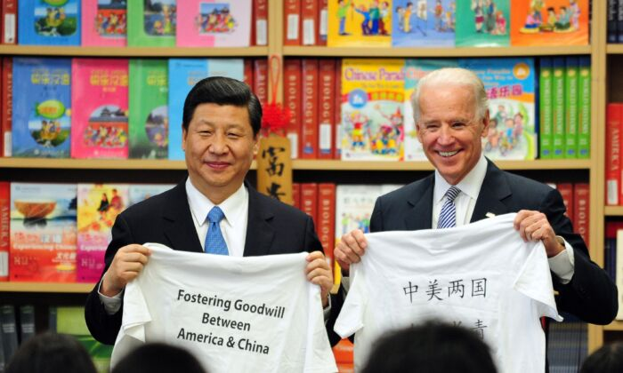 Then-U.S. Vice President Joe Biden and then-Chinese vice chair Xi Jinping display shirts with a message given to them by students at the International Studies Learning School in Southgate, outside Los Angeles, on Feb. 17, 2012. (FREDERIC J. BROWN/AFP via Getty Images)