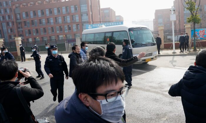 Journalists and security personnel gather near the entrance of the Wuhan Institute of Virology after a visit by the World Health Organization team in Wuhan in China's Hubei province, China, on Feb. 3, 2021. (Ng Han Guan/AP Photo)