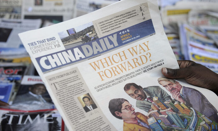 A newspaper consumer reads a copy of China's Africa edition of its daily newspaper infront of a news stand in the Kenyan capital on Dec. 14, 2012. (Tony Karumba/AFP via Getty Images)