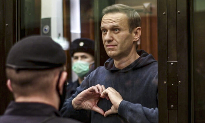 In this handout photo taken from a footage provided by Moscow City Court, Russian opposition leader Alexei Navalny shows a heart symbol standing in the cage during a hearing to a motion from the Russian prison service to convert the suspended sentence of Navalny from the 2014 criminal conviction into a real prison term in the Moscow City Court in Moscow, Russia, on Feb. 2, 2021. (Moscow City Court via AP)