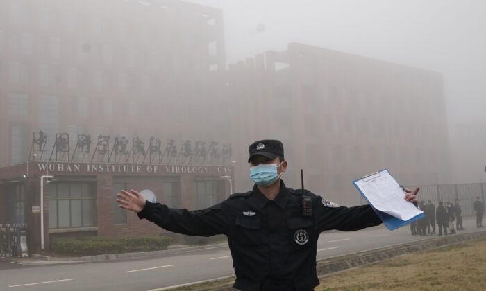 A security person moves journalists away from the Wuhan Institute of Virology after a World Health Organization team arrived for a field visit in Wuhan in China's Hubei Province, on Feb. 3, 2021. (Ng Han Guan/AP Photo)