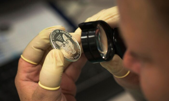 A quality control agent examines a 2013 enhanced silver eagle silver coin at the United States West Point Mint facility in West Point, N.Y., on June 5, 2013. (Shannon Stapleton/Reuters)