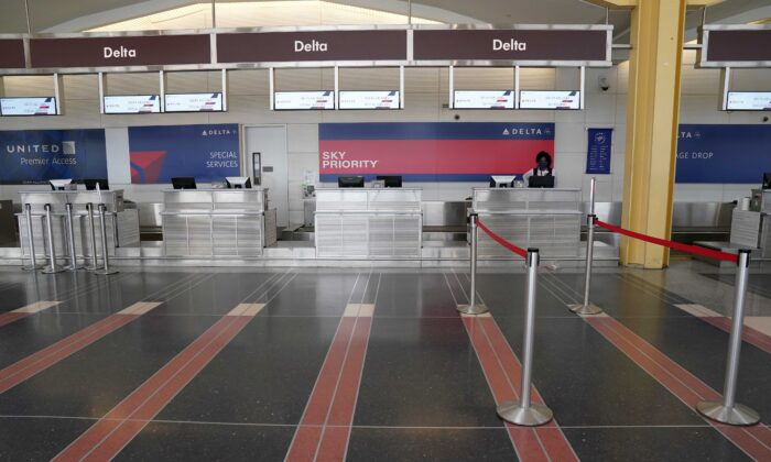 A customer service agent waits for customers at a Delta Airlines check-in counter at Washington's Reagan National airport, in Washington, on April 29, 2020. (Kevin Lamarque/Reuters)