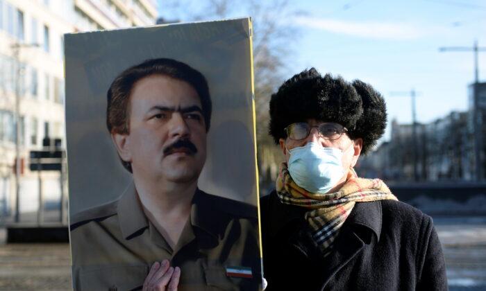 A man wearing a face mask holds a portrait of Iranian resistance leader Massoud Rajavi outside the court building in Antwerp, Belgium Feb. 4, 2021. (Johanna Geron/Reuters)