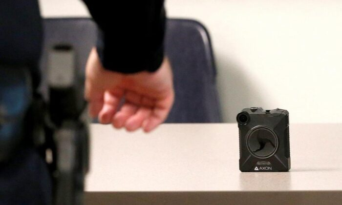 A Phoenix Police Department officer reaches for a new Axon Body 2 body camera as the precinct gets cameras assigned to them on July 3, 2019, in Phoenix. Outfitting RCMP officers with body-worn cameras at 700 detachments will cost an estimated $131 million over five years.(ROSS D. FRANKLIN/The Canadian Press/AP)