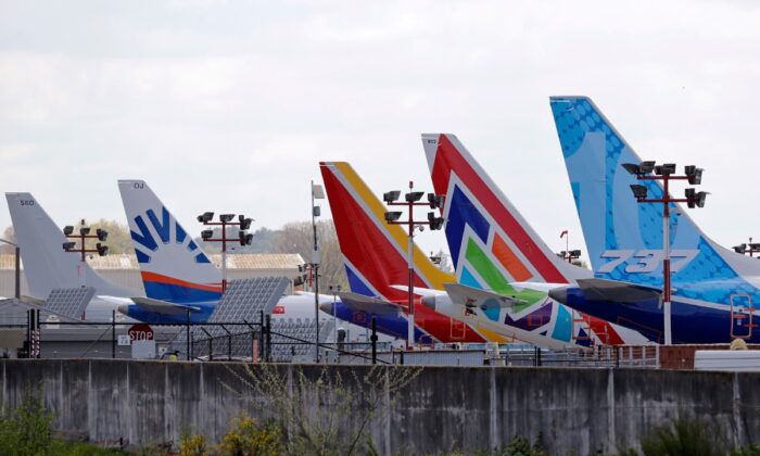 A line of Boeing 737 MAX jets sit parked on the airfield adjacent to a Boeing production plant in Renton, Wash., on April 20, 2020. (Elaine Thompson/File/AP Photo)