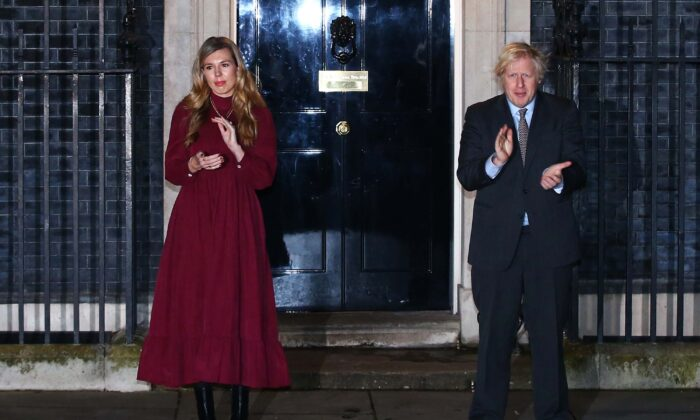 UK Prime Minister Boris Johnson and his fiancee Carrie Symonds take part in a doorstep clap in memory of Captain Sir Tom Moore outside 10 Downing Street on Feb. 3, 2021. (Hollie Adams/Getty Images)