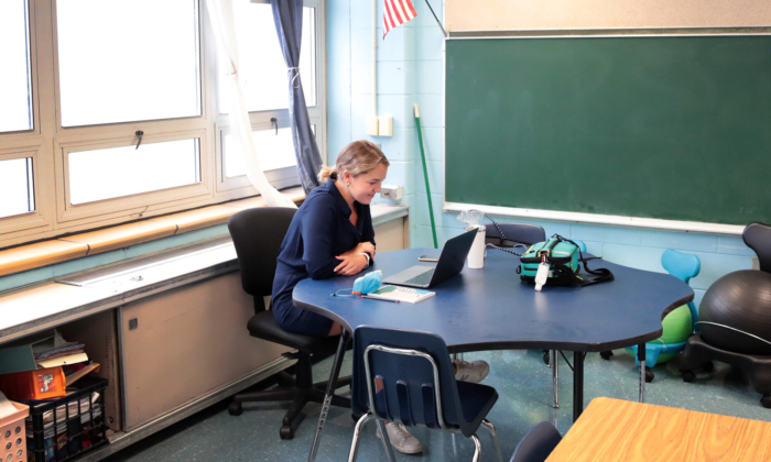 A teacher at King Elementary School sits in an empty classroom teaching her students remotely during the first day of classes in Chicago on Sept. 8, 2020. (Scott Olson/Getty Images)