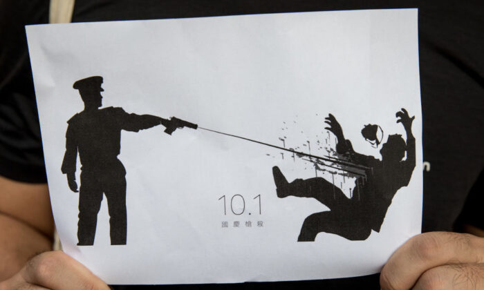 A man holds a sign depicting the shooting of a protester by a policeman during the Oct. 1 , 2019, protests in Hong Kong, China, on Oct. 2, 2019. (Chris McGrath/Getty Images)