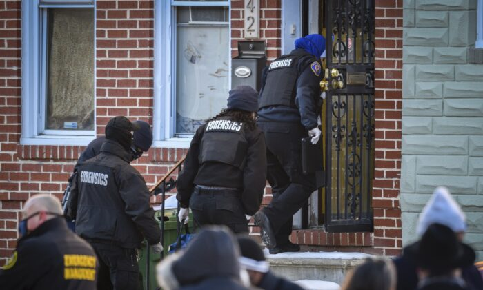 A Baltimore Police forensics team enters the house in West Baltimore where a U.S. Marshall was shot while serving an arrest warrant on Feb. 4, 2021. (Jerry Jackson/The Baltimore Sun via AP)