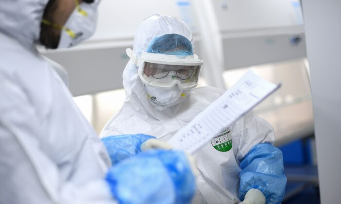 Laboratory technicians speak while working on samples to be tested for COVID-19 at a BGI laboratory in Wuhan, China, on Feb. 6, 2020. (STR/AFP via Getty Images)