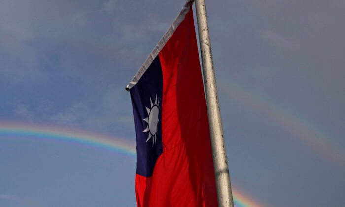 A double rainbow is seen behind a Taiwanese flag during the National Day celebrations in Taipei, Taiwan, on Oct. 10, 2017. (Tyrone Siu/Reuters)
