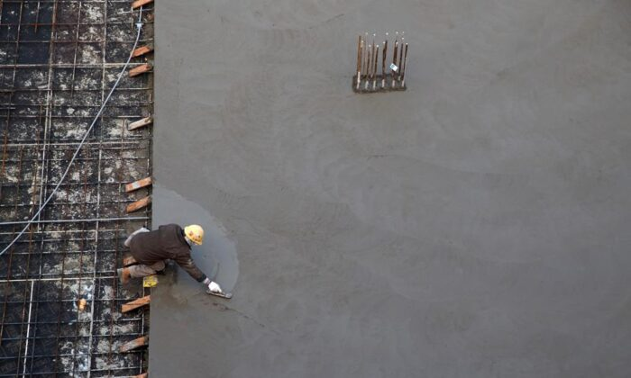 A worker smooths concrete at a residential housing construction site in Toronto on Jan. 16, 2020. (The Canadian Press/Cole Burston)