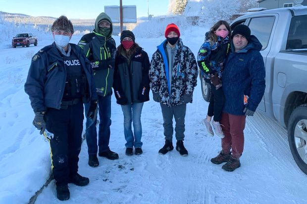 (L-R) Beaver Creek RCMP Cpl. Robert Drapeau, Gary Bath, Lynn Marchessault, Payton Marchessault, Rebecca Marchessault, and Tim Marchessault pose near the Canada-U.S. border crossing near Beaver Creek, Yukon. Bath, who gained widespread attention for helping drive the stranded American family to the Alaska-Canada border in November, will soon be able to do that trip in a new car. (The Canadian Press/HO, Gary Bath)